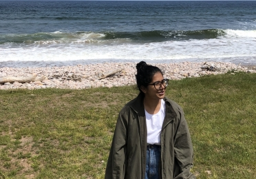 Person standing before ocean wearing glasses