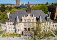 An aerial image of Denny Hall during the daytime with the UW Tower visible in the distance