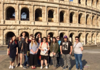 Students pose in front of the Roman colosseum